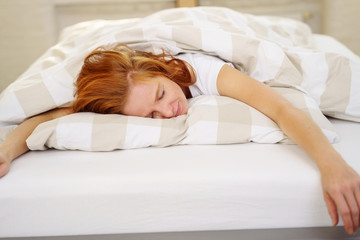 frau liegt zuhause im bett und schläft