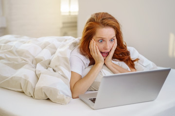 frau liegt im bett und schaut erschrocken auf ihren laptop