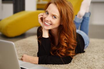 frau liegt auf dem fußboden im Wohnzimmer und arbeitet am laptop