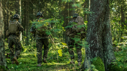 Squad of Five Fully Equipped Soldiers in Camouflage on a Reconnaissance Military Mission, Rifles in Firing Position. They're Moving in Formation Through Dense Forest. Back View Shot.