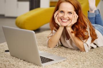 frau liegt in ihrer wohnung auf dem fußboden und surft im internet