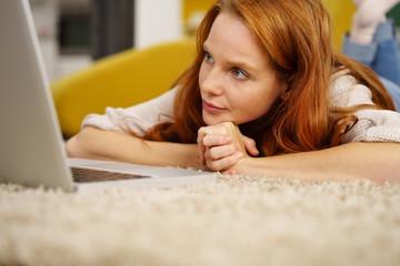 frau liegt auf dem boden in ihrer wohnung und schaut auf ihr notebook