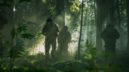 Fully Equipped Soldiers Wearing Camouflage Uniform Attacking Enemy, Rifles Ready to Shoot. Military Operation in Action, Squad Running in Formation Through Dense Smokey Forest.