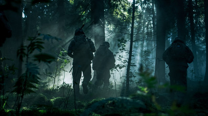 Squad of Five Fully Equipped Soldiers in Camouflage on a Reconnaissance Military Mission, Rifles in Firing Position. They're Running in Formation Through Dense Dark Forest. Side View Long Shot.