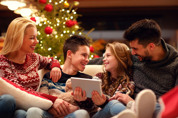Family together having fun for Christmas with tablet