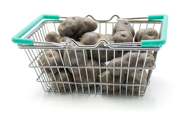 Vitelotte potatoes in a shopping basket isolated on white background.