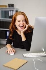 geschäftsfrau sitzt am schreibtisch und zwinkert lachend mit einem auge