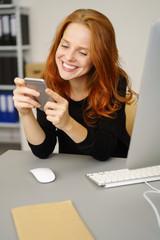 geschäftsfrau schaut zufrieden auf ihr smartphone