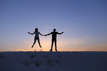Cheerful guy and girl having fun and dancing on top of sand dune