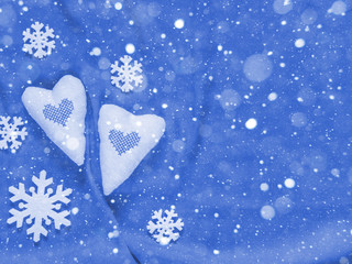 Two soft hearts and white snowflakes on a blue background. Christmas background. Valentine's day background. Free space for text. Top view