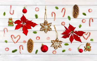 Christmas decoration. Flower of red poinsettia, branch christmas tree, christmas balls, gingerbread, candy canes and cones spruce on background of white painted wooden planks. Top view, flat lay.