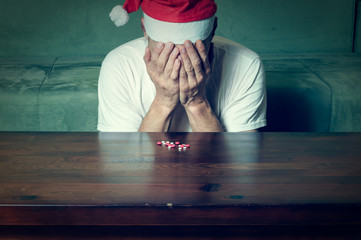 Young man with Santa Claus hat suffering from suicidal depression feeling lonely and sad for New Year and Christmas holiday suicide concept