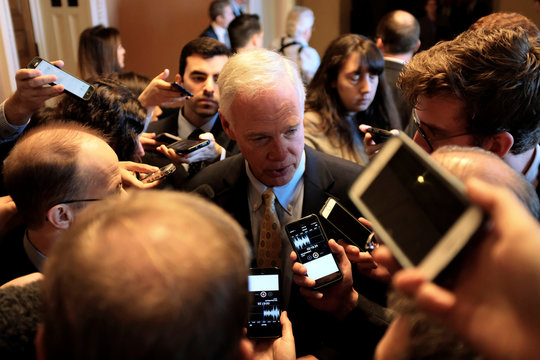 U.S. Senator Ron Johnson (R-WI) speaks to reporters on his way to the Senate floor for debate over the Republican tax reform plan in Washington