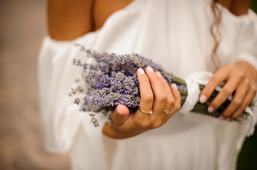 Woman in white dress holding in hands a bouquet of lavender