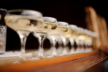 Set of elegant glasses with champagne arranged in line