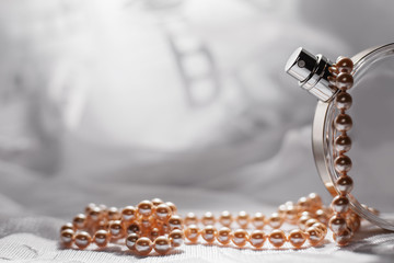 Perfume in a glass bottles and pearl beeds