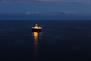 Offshore oil drilling rig on the south cost of Tenerife island on the North Atlantic Ocean. The sun has set revealing a beautiful light show