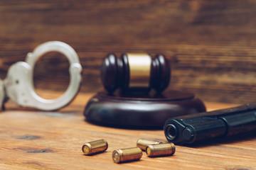 Judge gavel, handgun and handcuffs on wooden background
