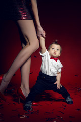 sexy girl in red short dress with a boy child on a red background