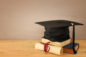 Image of graduation black hat over old books next to graduation on wooden desk. Education and back to school concept.