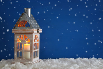 Wooden old house with candle over the snow and blue background.