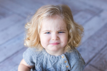 Beautiful toddler girl frowns. Сlose-up portrait. Blue eyes.