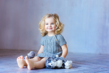 Young pretty girl sitting on a floor. Smiling. Indoor. Toddler girl.