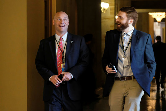 White House Director of Legislative Affairs Short speaks with a reporter as he walks toward the Senate floor during debate over the Republican tax reform plan in Washington
