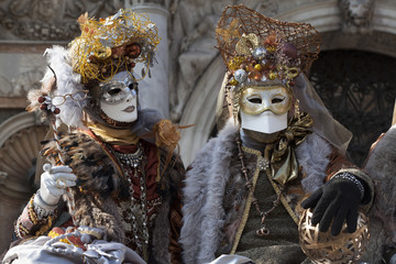Venice Carnival characters in a colorful brown and gold Carnival costumes and masks Venice Italy