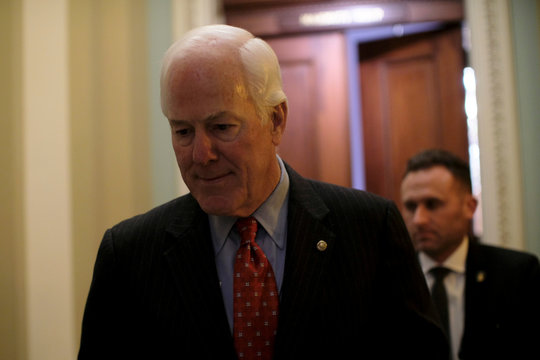 U.S. Senate Majority Whip Cornyn walks from his office to the Senate floor during debate over the Republican tax reform plan in Washington
