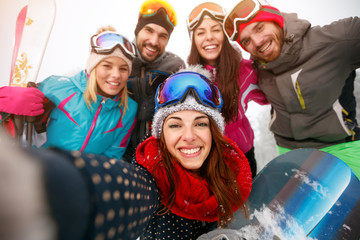 happy friends having fun on snow. Snowbarders and skiers group team making selfie