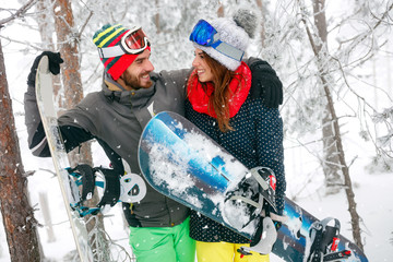 couple snowboarder having fun in the fog winter forest