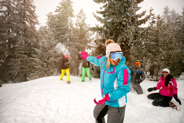 group of cheerful friends having snow fighting and fun in snowy mountain