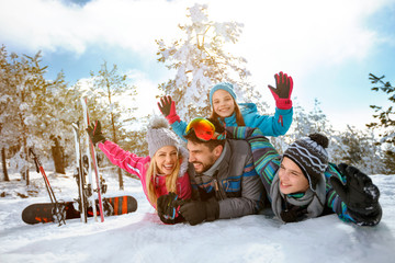 smiling family enjoying winter vacations in mountains on snow
