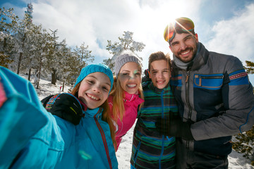 family laughing and making selfie on winter ski vacation
