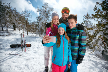 family smiling and making selfie with mobile on winter ski vacation