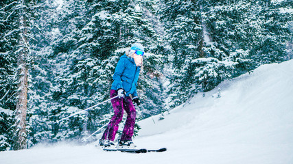 16x9 wild screen. Girl skiing during snowing weather in ski resort in Utah, USA. Skier wearing blue winter jacket, purple warm pants, blue beanies and white gloves. Tree covers by snow.