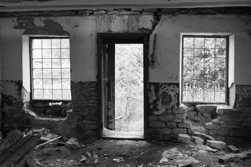 Windows with bars and an open door of an abandoned building from the inside black and white photo