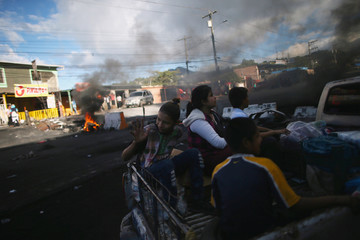 People pass next to burning tires as supporter of presidential candidate Salvador Nasralla take part during a protest caused by the delayed vote count for the presidential election at Villanueva neighborhood in Tegucigalpa
