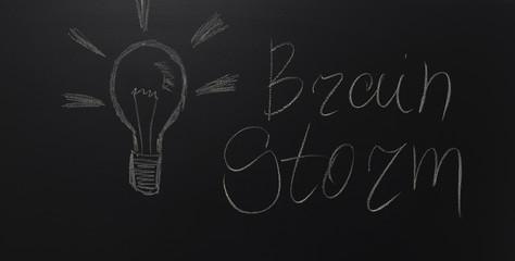 drawn light on blackboard with the text: Brain Storm