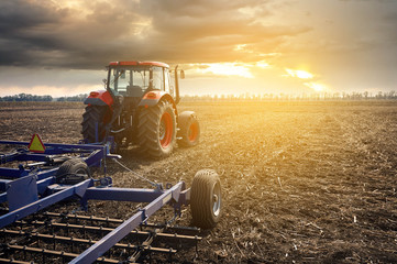 Fototapete - Tractor working in the field on a sunset background