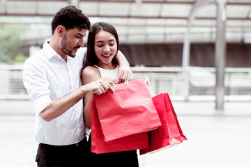 Happy couple cheering after a hard day of huge sale shopping in asian country.