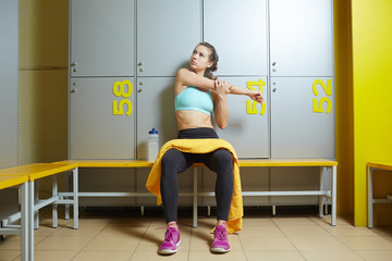 Young sportswoman in changing room warming up before training in gym