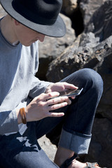 Young man in black hat checks messages on smartphone