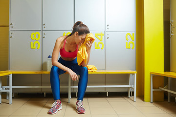 Really tired girl in leggins and sports tanktop drying her wet face with towel in dressing-room