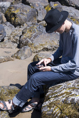 Young man in black hat checks messages in social networks on the ocean shore