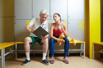 Mature trainer showing young woman her new sport results and comparing them with the latest ones