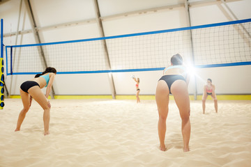 Back view of volleyball players standing on sand field with bent knees ready to attack the ball