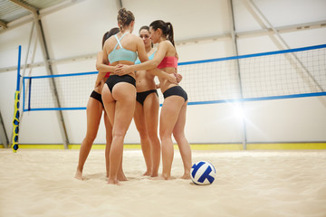 Young volleyball players making circle while consulting about details of game
