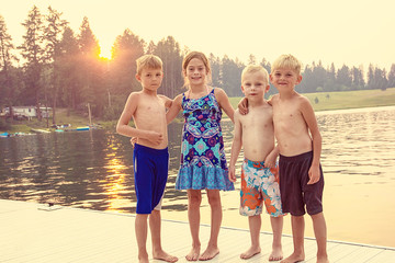 Four cute kids enjoying their summer vacation together at the lake. Playing together on the dock at sunset on a warm evening